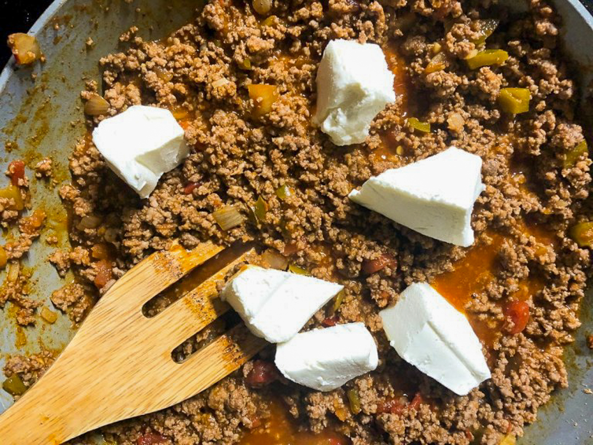 adding cream cheese to ground beef mixture